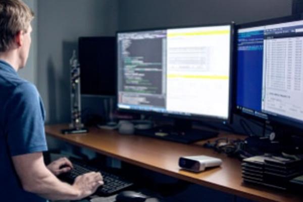 Hombre trabajando en varias computadoras